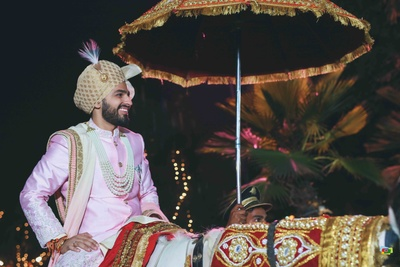 Groom in his baraat in a pink sherwani and contrast off white colored safa