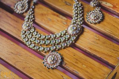 Three stand polki set studded with polki diamonds and green stones with drop pendants