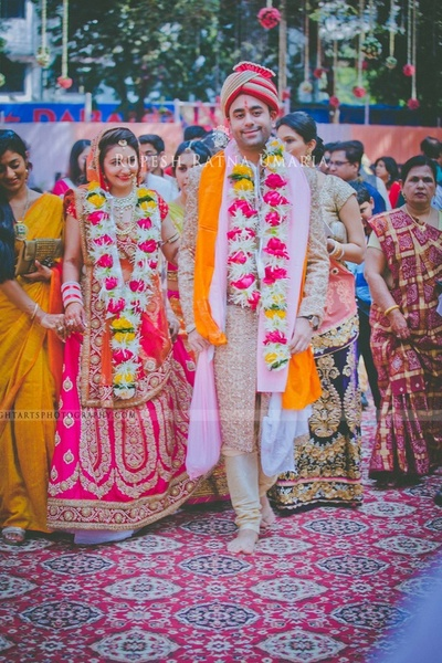 Newlyweds strung in dense floral garlands