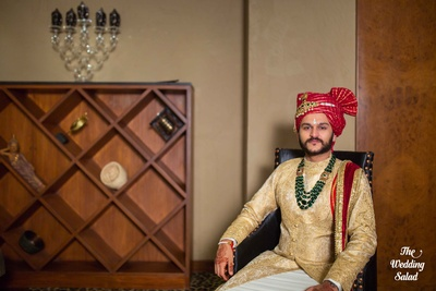 Royal Indian groom in red safa and beige outfit for the wedding