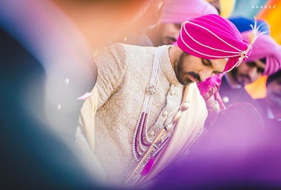 Aman wearing royal white and gold sherwani styled with pearl neck piece and pink turban.