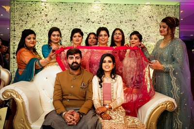 the bride and groom with family during the engagement ceremony