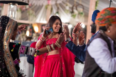 The bride and groom shaking a leg with Rajasthani dancers at their post-wedding dinner.