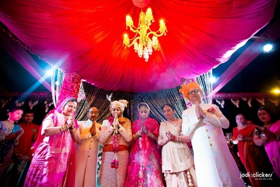 Canopy style draped red mandap with a crystal chandelier and pink clustered floral arrangement on the pillars for the grand wedding ceremony held at Hotel Fairmont, Jaipur