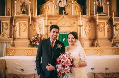 Couple dressed in black and white wedding outfits styled with a red bridal bouquet