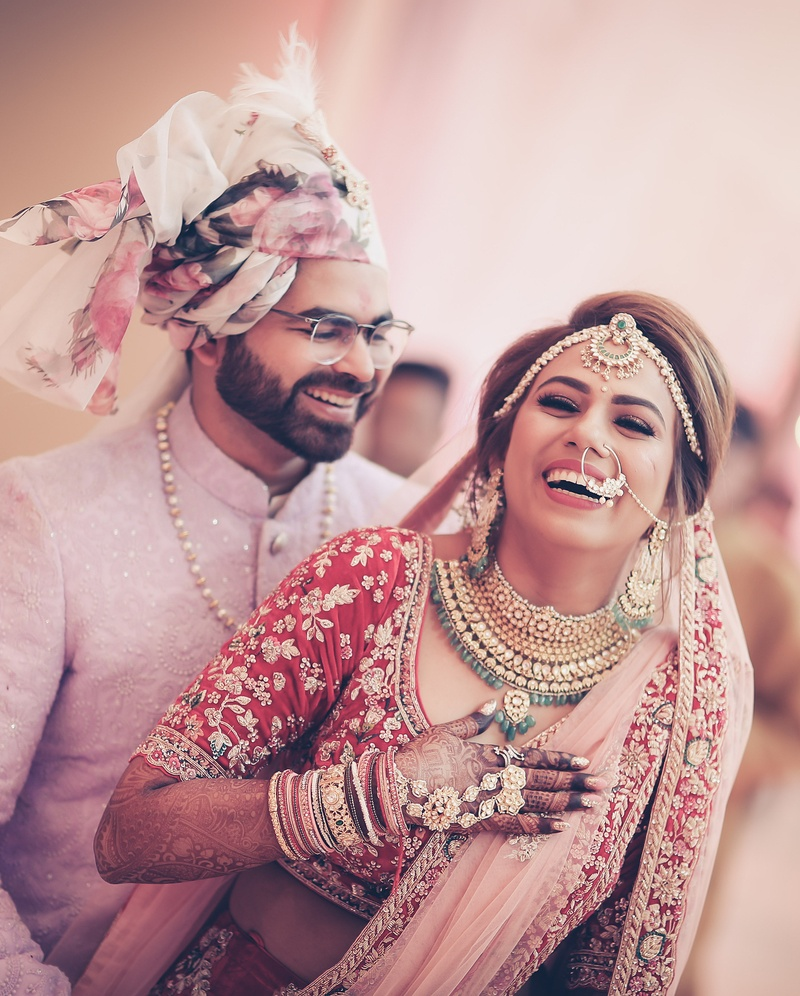 Indian wedding couple poses to click during the varmala ceremony