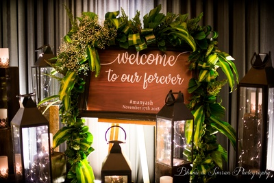 A rustic cocktail signage to welcome the guests decorated with baby breaths, lamps and foliage.