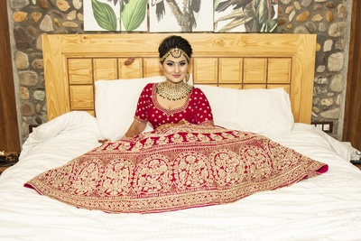 The bride looks stunning in her traditional red lehenga.