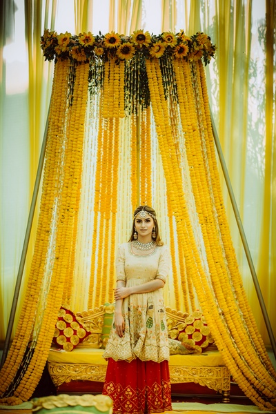 The bride looks absolutely stunning in an offwhite kurta and red sharara against an all-yellow backdrop!
