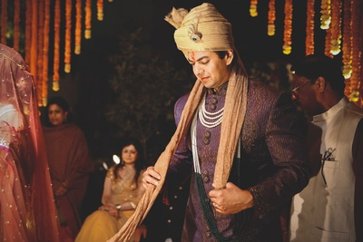 Grooms wear styled with purple textured wedding sherwani, organza tissue Safa and elongated moti haar against the garland