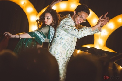 A candid picture of the couple shaking a leg and having fun at their sangeet
