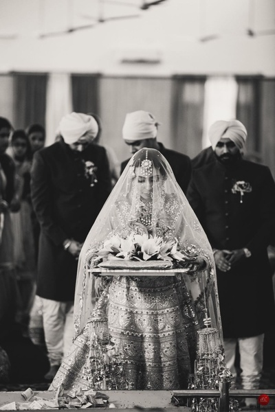 Traditional bride carrying the puja thaal for the gurudwara wedding