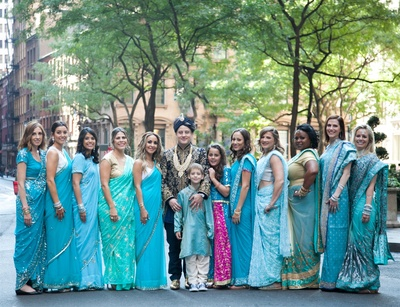 martin with his bridesmaids dressed in blue sarees for the wedding ceremonies