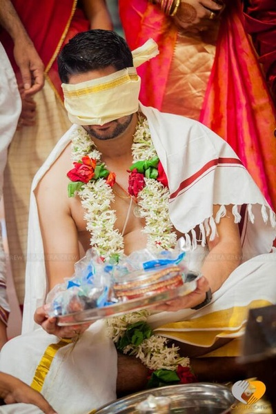 Groom blind folded for wedding ritual graced with a floral garland wearing the traditional white lungi with a gold border and an angavastra