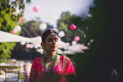 beautiful picture of the bride highlighting her emerald jewelery and pink lehenga