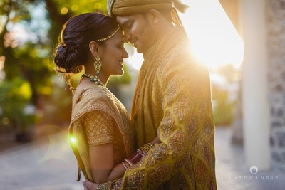 Dressed in coordinated gold and ocher wedding outfits for their outdoor day wedding
