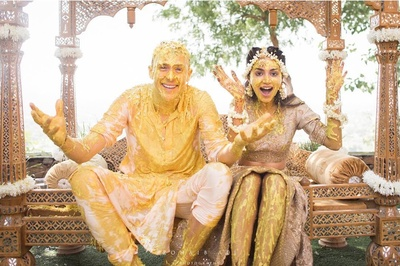 bride and groom in a fun pose for the haldi ceremony