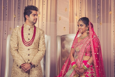 Groom paired his golden Sherwani with Pink multi stringed neckpiece, complementing the bride.