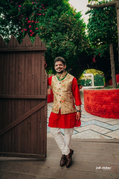 The groom looks dapper in this 1blue kurta paired with a floral ochre jacket.