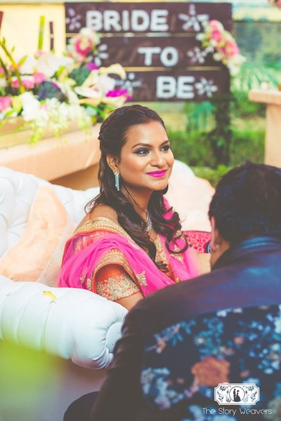 Bronze toned bridal makeup with bold pink lips and well defined kohl eyes for the outdoor mehndi ceremony