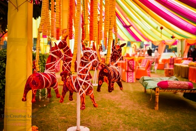 Mehendi function entrance of yellow and orange genda and Indian props