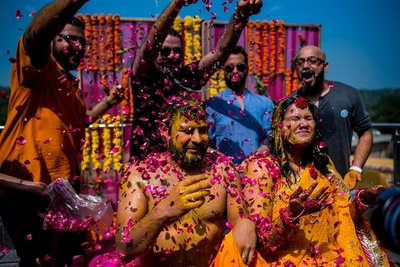 the bride and groom being showered with flower petals at the haldi ceremony