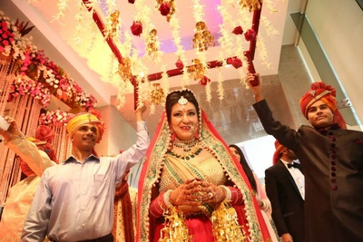 Being escorted with a floral decorated canopy and gold kalira latkans