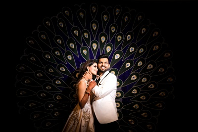 The couple looks stunning against the peacock inspired backdrop!
