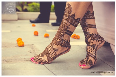 Feet adorned with bridal mehendi intricately patterned with swirls and floral design