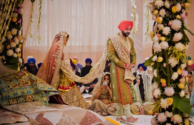 The bride and groom taking pheras during their Anand Karaj ceremony at the gurudwara