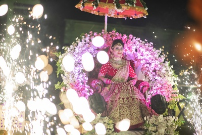 The bride making a grand entry in a traditional-style palki.