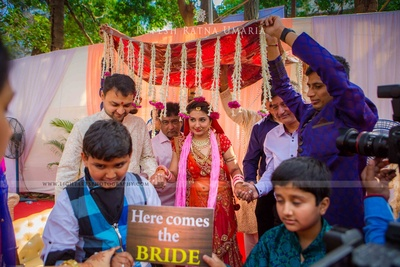 Bride being escorted under a chaddar bordered with strings of Jasmine