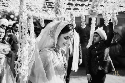black and white picture of the bride while she is entering the venue under a phoolon ki chadaar