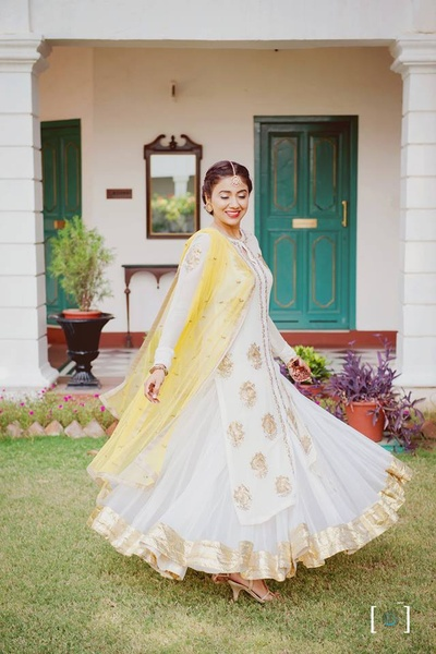 Twirling sister of the bride in pure white and gold anarkali for the wedding day.