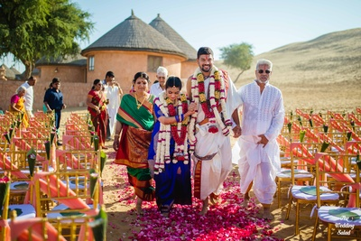 The bride and groom walking on a path full of flower petals post their jaimala ceremony.