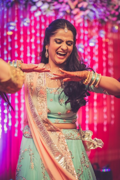 Bride Vasundhra looking pretty in this aqua blue lehenga with pastel pink dupatta styled with diamond earrings and necklace for her sangeet ceremony.