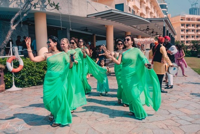 Bride and bridesmaids dancing as they enter the wedding mandap