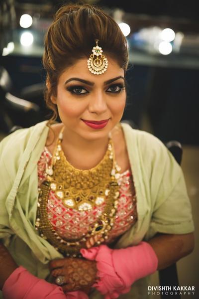 Flawless pretty pink makeup and a beautiful kundan maang tikka for the wedding day.