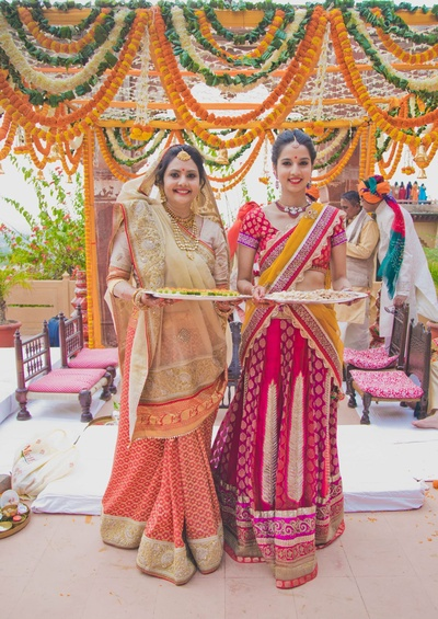 Meera Mahadevia  decked in a cream and red saree and her younger daughter in a yellow and red embellished lehenga