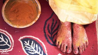Mehendi and haldi painted across bride's feet