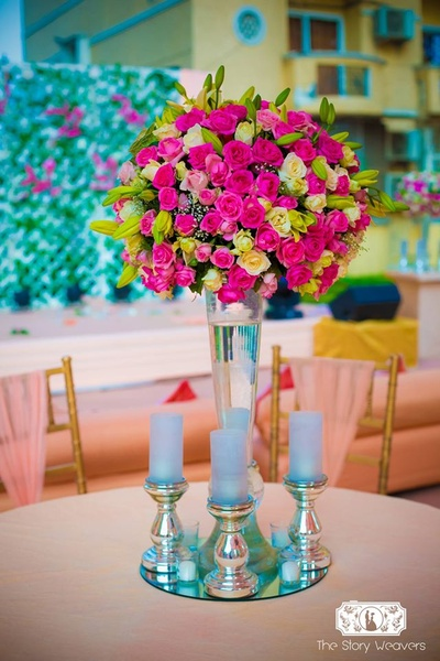 Floral Table centerpiece adorned with fresh pink and yellow roses and green buds - accentuated with pastel blue candles on silver candle stands