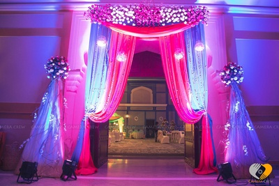 Entrance decor ideas for Sangeet ceremony, festooned with pink and blue drapes, clustered floral arrangement and pomender style flowers