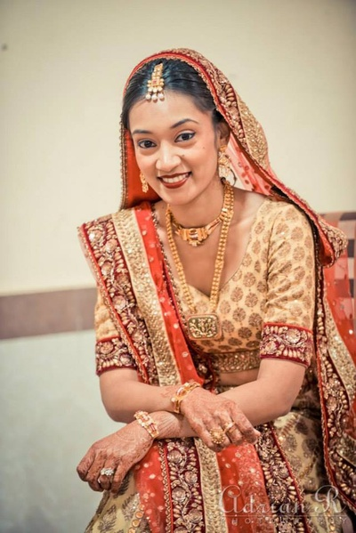 Traditional gold jewellery worn with a beige and orange bridal lehenga