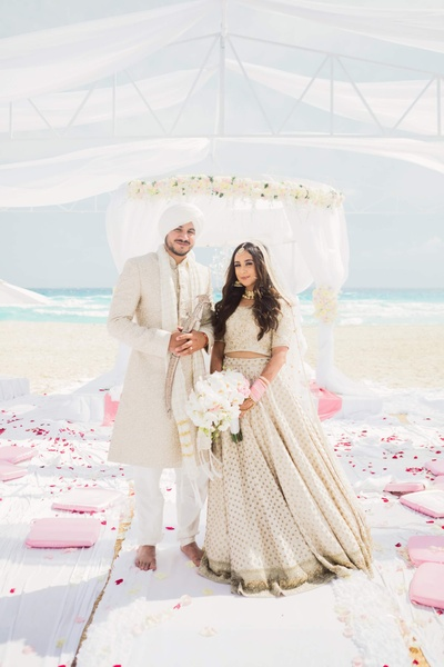 Bride and groom pose together post the wedding at their beach mandap