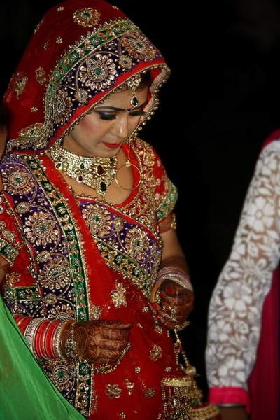 Heavily embellished red bridal saree featuring a blue and green patterned border