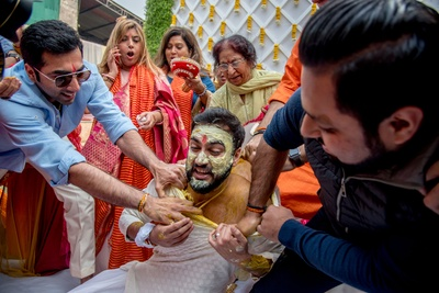 The family tearing the groom's clothes as part of the haldi ceremony.
