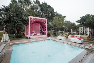 A pool side peppy and vibrant pink mandap for the bride's mehendi!