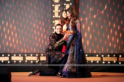 Blue and gold sangeet lehenga bedecked with zari motifs, loose curls and diamond jewellery. Groom dressed in an embroidered achkan to match the bride's outfit