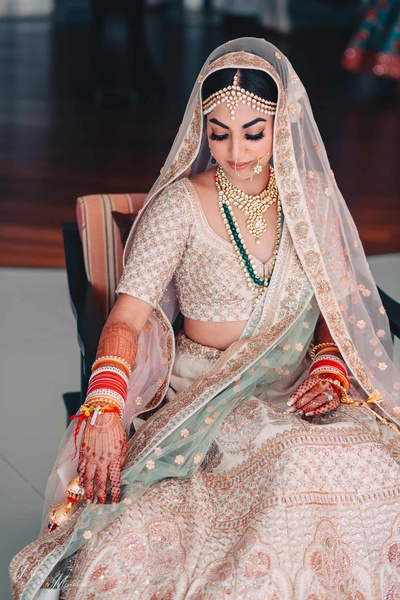 Simi posing in her minimal and natural makeup look paired with her ivory and blue lehenga