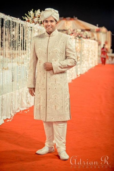 Heavily detailed off-white wedding sherwani and cream safa with pearl danglers
